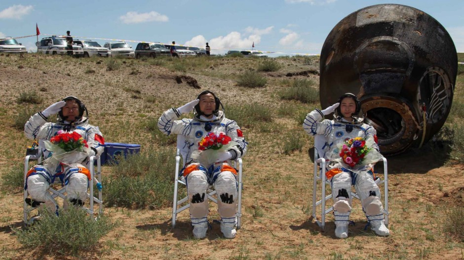 Chinese astronauts Jing Haipeng, Liu Wang and Liu Yang, China's first female astronaut, salute in front of the re-entry capsule of China's Shenzhou 9 spacecraft in Siziwang Banner, Inner Mongolia Autonomous Region