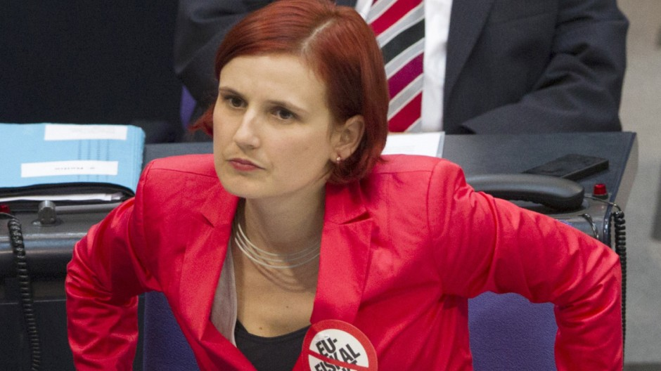 The co-leader of Die Linke party Kipping wears sticker denouncing EU fiscal pact as she listens to Chancellor Merkel deliver government policy statement in in parliament in Berlin