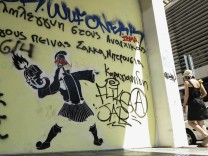 A woman walks beside a wall covered in graffiti in central Athens
