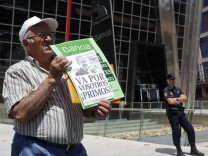 A minority shareholder protests against the abuses of banks and saving banks in front of the headquarters of Spain's lender bank Bankia in Madrid