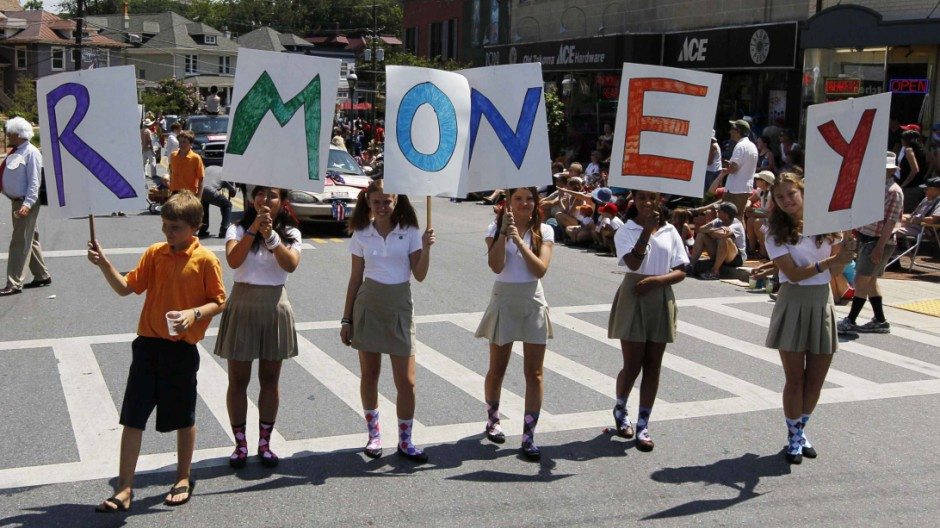 A group of young people parody U.S. Republican presidential candidate Romney's last name as R-MONEY as they march in a Fourth of July parade in Takoma Park