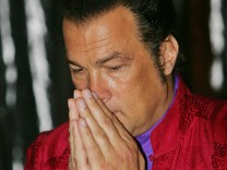 Actor Seagal greets journalists during news conference to promote his album in Bangkok