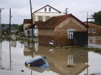 A car lies submerged in a flooded street in the village of Novoukrainsk