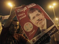 A supporter of Egypt's first Islamist President Mohamed Mursi cheers with a poster of Mursi at Tahrir Square in Cairo