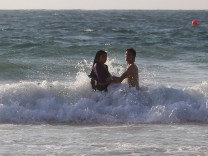 A couple swims in the water on a public beach in Alexandria