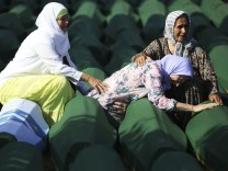 Bosnian Muslim women sit and cry near the coffin of their relatives at Memorial Center in Potocari before a mass burial, near Srebrenica