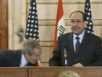Video frame grab of U.S. President George W. Bush ducking from a shoe during a news conference in Baghdad