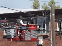 Law enforcement officers use a fire truck lift to inspect the apartment where suspect James Eagan Holmes lived in Aurora