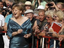 German Chancellor Merkel signs autographs as she arrive for opening of Bayreuth Wagner opera festival in Bayreuth