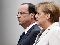 German Chancellor Merkel and French President Hollande listen to national anthems during a ceremony at the Chancellery in Berlin