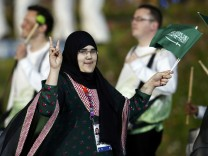 Saudi Arabia's Wojdan Ali Seraj Abdulrahim Shaherkani gestures as she walks with the contingent in the atheletes parade during the opening ceremony of the London 2012 Olympic Games at the Olympic Stadium