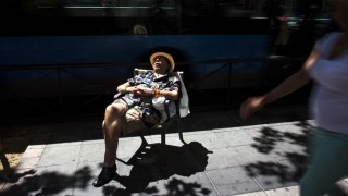 A man wearing a wristband of the Spanish flag dozes off in a public chair in Madrid