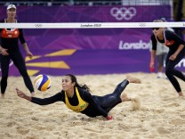 Brazil's Talita saves the ball against Madelein Meppelink and Sophie van Gestel during their women's beach volleyball preliminary round match at the London 2012 Olympics Games at the Horses Guards Parade