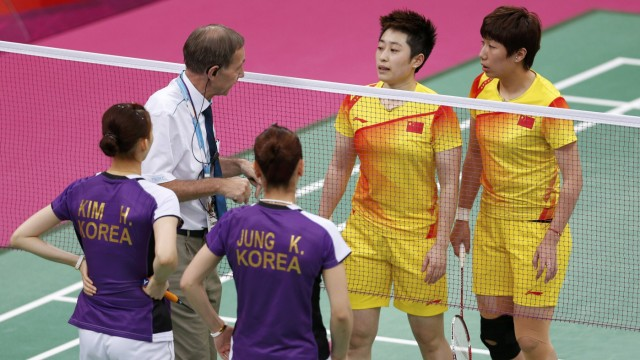 Tournament referee Torsten Berg speaks to players from China and South Korea during their women's doubles badminton match during the London 2012 Olympic Games at the Wembley Arena