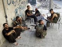 Free Syrian Army fighters take a break from fighting with forces loyal to Syrian President Assad in downtown Aleppo