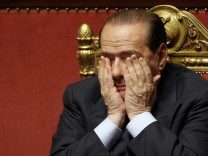 File picture shows Italian Prime Minister Berlusconi covering his face during a vote of confidence at the Senate in Rome