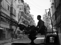 A Free Syrian Army fighter mans an anti-aircraft gun during a break in clashes with Syrian Army soldiers in the Salah al-Din neighbourhood in central Aleppo