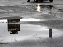 The headquarters of German car manufacturer Opel are reflected in a puddle in Ruesselsheim