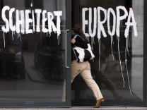 Woman enters Academy of Arts in Berlin that features graffiti quoting German Chancellor Merkel