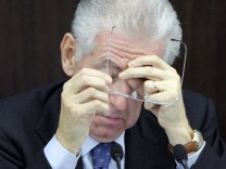 Italian Prime Minister Monti takes his glasses during a news conference on the new austerity package in Rome