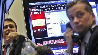A television screen displays the decision of the Federal Reserve rate as traders work on the floor of the New York Stock Exchange