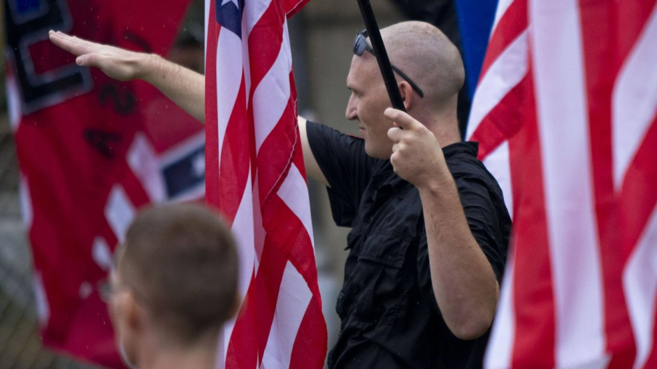 A member of a white supremacy group gives the fascist salute during a gathering in West Allis