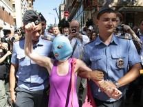 A supporter of the female punk band 'Pussy Riot' is detained by police outside a court in Moscow