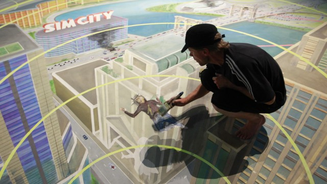 A worker paints at the exhibition stand of 'Sim City' during the Gamescom 2012 fair in Colognee