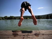 Ein junger Mann springt am Montag (18.06.2012) mit Kopfsprung in einen Badesee in Plüderhausen (Rems-Murr-Kreis)