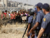 Police look on as women carry placards in protest against the killing of miners by the South African police on Thursday, outside a South African mine in Rustenburg