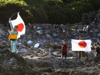 Members of a Japanese nationalist group raise flags as they land on Uotsuri island, part of the disputed islands in the East China Sea