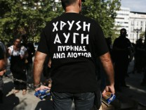 A supporter of Greece's Golden Dawn extreme right party distributes packs of pasta to residents suffering from the economic crisis at the Syntagma square in Athens