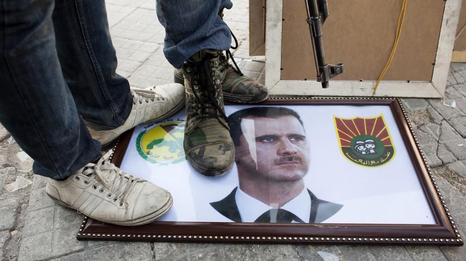 Syrische Rebellen treten in Aleppo auf ein Assad-Porträt