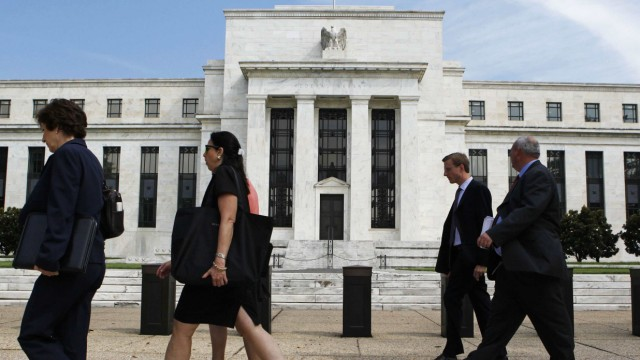 People walk past the Federal Reserve in Washington