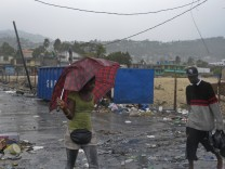 Haitian woman tries to shield herself from heavy rains of Tropical Storm Isaac with an umbrella in Port-au-Prince