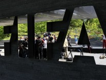 TV camera teams and journalists are reflected in a FIFA sign as they interview Zwanziger, member of the FIFA's executive committee after a committee meeting in Zurich