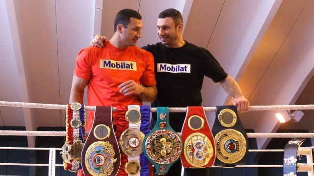 Ukranian heavyweight boxers Vladimir and Vitali Klitschko pose with their world championship titles belts at training camp in Going