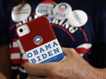 A woman holds a smartphone as U.S. President Barack Obama speaks during a campaign event at Truckee Meadows Community College in Reno