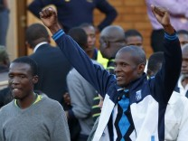 Miners and their supporters celebrate after being released outside the court in Ga Rankuwa, near Pretoria