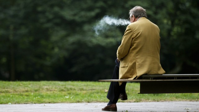 A man smokes a cigarette during a pause in the senior delegates meeting of the conservative Christian Democratic Union (CDU) in the western city of Recklinghausen