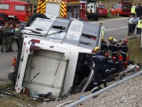 French gendarmes and firemen inspect a bus after an accident on the A-36 motorway in Sausheim near Mulhouse
