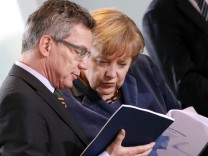 German Defence Minister de Maiziere shows files to Chancellor Merkel at a cabinet meeting at the Chancellery in Berlin