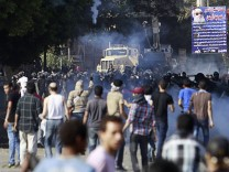 Protesters run from tear gas released by riot police during clashes along a road leading to the U.S. embassy, near Tahrir Square in Cairo