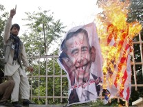 Afghan protesters set fire to a U.S. flag as they shout slogans during a demonstration in Kabul