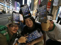 Men wearing cardboard hats, depicting Apple's new iPhone 5, pose for photos as they wait for the release of the phone near Apple Store Ginza in Tokyo