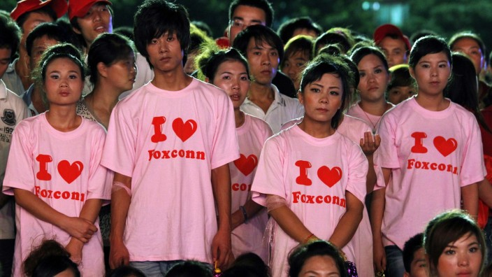File picture shows workers from Foxconn taking part in a 'Treasure Your Life' rally inside a stadium at a Foxconn plant in Longhua