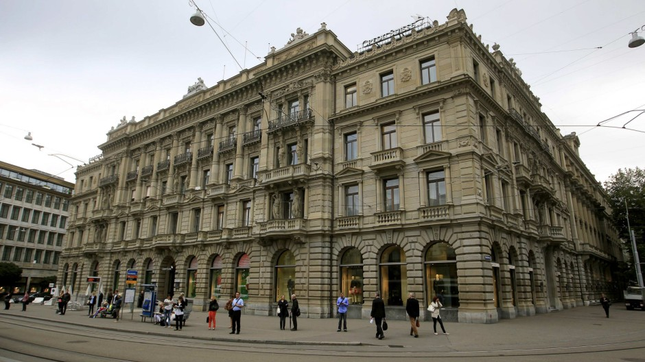 File photo of people standing at a tram stop in front of the headquarters of Swiss bank Credit Suisse in Zurich