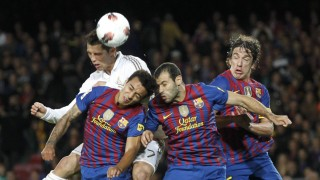Real Madrid's Ronaldo heads the ball with Barcelona's Thiago, Mascherano and Puyol during their Spanish first division soccer match in Barcelona