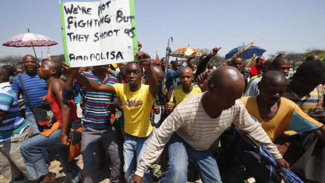 Striking platinum miners march near the Anglo-American Platinum (AMPLATS) mine near Rustenburg in South Africa's North West Province