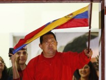 Venezuelan President Hugo Chavez waves the national flag while celebrating from a balcony at the Miraflores Palace in Caracas